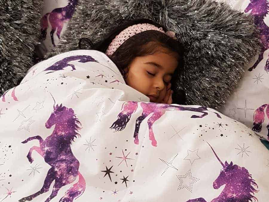 Young girl sleeping in a bed with purple unicorn duvet
