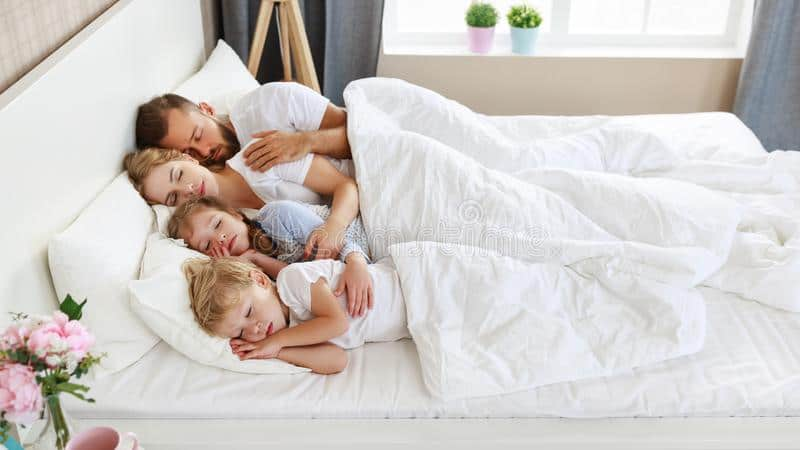 family asleep in bed with white sheets